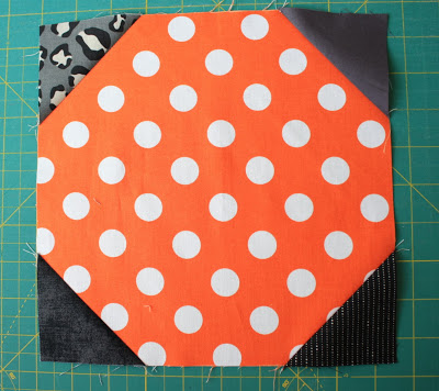 Kết quả hình ảnh cho Take four of the 2 3/4″ x 2 3/4″ black squares and draw one diagonal line across them. Place them in the four corners of the 9 1/2″ x 9 1/2″ orange blocks. Sew directly on all four diagonal lines.